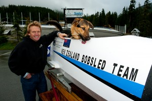 Martin White olympic contender and his temporary bobsled crew member -dog Harley -polishing the sled